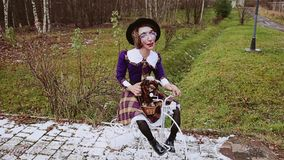 Funny and fun doll of a woman, sitting on a bicycle. A funny parody. The doll is clearly parodying someone. The facial features are specially distorted. The stock video footage