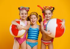 Funny funny happy children  jumping in swimsuit  jumping  on col. Funny funny happy children  jumping in swimsuit and swimming glasses jumping on colored Royalty Free Stock Photos
