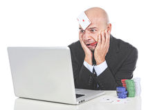 Funny gambling addict businessman betting with poker chips and cards on laptop Stock Images