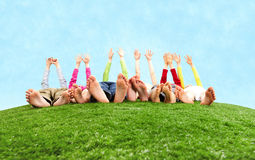 Funny game. Image of several children lying on the grass and stretching their hands to the sun Royalty Free Stock Photo