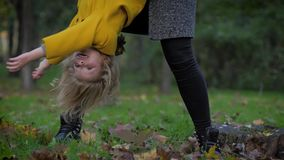 Funny game, portrait of a joyful beautiful girl playing with her mother in park in autumn season