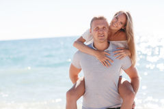 Funny games happy couple in love on the beach. Happy loving couple,young blond men and women having fun at the beach, the blue ocean,a girl is sitting on the stock image