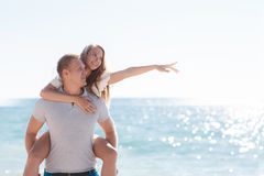Funny games happy couple in love on the beach. Happy loving couple,young blond men and women having fun at the beach, the blue ocean,a girl is sitting on the stock photo