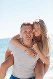 Funny games happy couple in love on the beach. Happy loving couple,young blond men and women having fun at the beach, the blue ocean,a girl is sitting on the stock photos