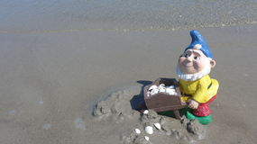 Funny garden dwarf with wheelbarrow on the beach Royalty Free Stock Images