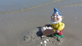 Funny garden dwarf with wheelbarrow on the beach Stock Images