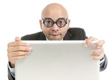 Funny geek and freak bald head businessman with computer laptop wearing thick glasses looking nerd. And silly in phobia to technology and internet isolated on Stock Photography