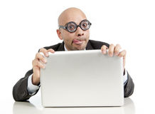 Funny geek and freak bald head businessman with computer laptop wearing thick glasses looking nerd. And silly in phobia to technology and internet isolated on Royalty Free Stock Photography