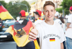 Funny german fan showing thumb with other fans Royalty Free Stock Image