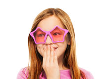 Funny giggling girl in glasses with star frames. Pretty giggling young girl which looking aside in pink spectacles with star frames isolated on white Royalty Free Stock Images