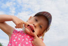 Funny girl. Girl puts one's tongue out on blue sky background Royalty Free Stock Images