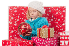 Funny girl around christmas boxes with red ball Royalty Free Stock Images