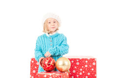 Funny girl around christmas boxes with red ball Royalty Free Stock Photos