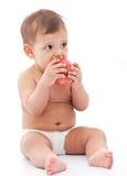 Funny girl baby eating an apple. Stock Photos
