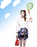 Funny girl with a balloon. Beautiful girl holding a balloon in one hand and red shoes in another, blue gradient background with clouds Stock Photography