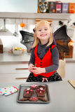 Funny girl in bat costume holding freshly Halloween cookies Royalty Free Stock Photography