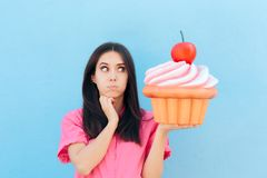 Funny Girl with Big Cupcake Thinking of her Diet. Woman holding big backed dessert on cheat day stock image