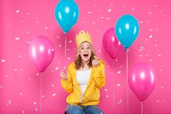 Funny girl in birthday hat, balloons and flying confetti on pastel pink background. Attractive teenager celebrating birthday. Funny girl in birthday hat royalty free stock image