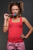Funny girl bitting motley lollipop Royalty Free Stock Image