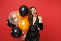Funny girl in black dress celebrate showing tongue blink hold mobile phone with blank black empty screen air balloons. On red background. Happy New Year stock photography