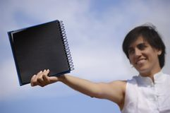 Funny girl with a black notebook. In a blue sky Royalty Free Stock Photos