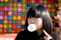 Funny girl blowing a bubble gum. Outdoor stock image
