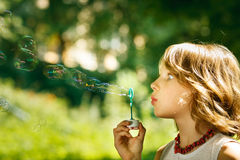 Funny girl blowing soap bubbles outdoors Royalty Free Stock Photo
