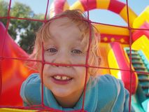 Funny girl in bounce castle. Funny girl playing in a big bounce castle Royalty Free Stock Image