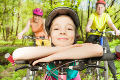 Funny girl bracing against handlebar of  the bike. Portrait of happy smiling girl in bicycle helmet, bracing against handlebar of the bike Royalty Free Stock Images