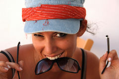 Funny girl with broken sunglasses. Pretty girl with funny expression holding a pair of broken sunglasses with her teeth Stock Image