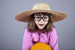 Funny girl in cap and glasses keeping pumpkin. Royalty Free Stock Photo
