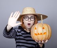 Funny girl in cap showing pumpkin. Stock Photography