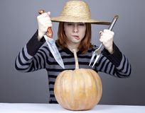 Funny girl in cap try to eat a pumpkin. Stock Photography