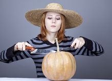 Funny girl in cap try to eat a pumpkin. Royalty Free Stock Image