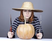 Funny girl in cap try to eat a pumpkin. Royalty Free Stock Photo