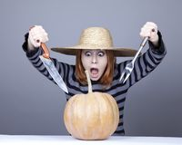 Funny girl in cap try to eat a pumpkin. Stock Image