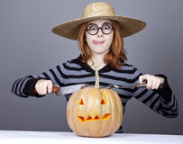 Funny girl in cap try to eat a pumpkin. Royalty Free Stock Photos