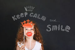 Funny girl with carnival crown and lips showing her teeth, stand Royalty Free Stock Photos
