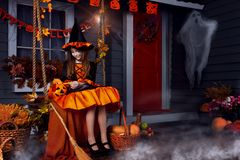 Kid in halloween witch costume ready for halloween. Funny girl child kid in halloween witch costume with black hat and orange pumpkins basket with spooky face Royalty Free Stock Photography