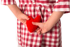Funny Girl child in red plaid dress with red crocheting heart, Royalty Free Stock Photo