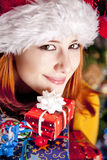 Funny girl in christmas cap with gift boxes Stock Images