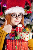 Funny girl in christmas cap with gift boxes Royalty Free Stock Images