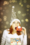 Funny girl in christmas cap with gift boxes Royalty Free Stock Image
