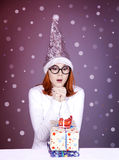 Funny girl in christmas cap with gift boxes Stock Photography