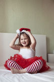 Funny girl in a Christmas cap and striped pants on the bed, Stock Photography