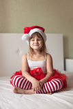 Funny girl in a Christmas cap and striped pants on the bed, Royalty Free Stock Image