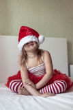 Funny girl in a Christmas cap and striped pants on the bed, Royalty Free Stock Photos
