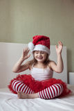 Funny girl in a Christmas cap and striped pants on the bed, Stock Image