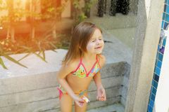 Funny girl close eyes, drops of water fall on little kid in swimsuit shower on sunny day outside. Funny kid close eyes, portrait of water drops fall on little Stock Photo