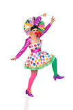 Funny girl clown with a big colorful wig dancing Stock Images